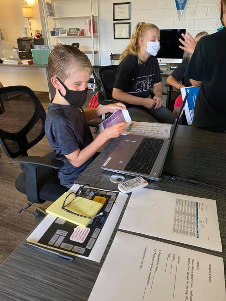Students in masks work in groups with students using a computer.